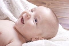 在被编织的毯子包裹的兴高采烈的男婴 库存图片