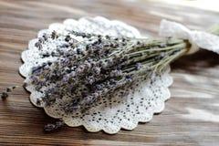 在被编织的餐巾,木桌,葡萄酒de的干燥淡紫色花束 库存照片