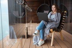 在被编织的床罩包裹的惊奇妇女开会使用膝上型计算机 库存图片