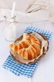 在被编织的板材的新鲜的被烘烤的新月形面包在白色木backgrou 图库摄影