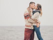 在被编织的毛线衣的年轻有吸引力的夫妇在海岸的峭壁 库存图片