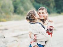 在被编织的毛线衣的年轻有吸引力的夫妇在海岸的峭壁 库存照片