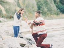 在被编织的毛线衣的年轻有吸引力的夫妇在海岸的峭壁 图库摄影