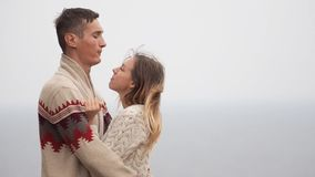 在被编织的毛线衣的年轻有吸引力的夫妇在海岸,戏弄,拥抱和亲吻的峭壁 影视素材