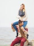 在被编织的毛线衣的年轻有吸引力的夫妇获得乐趣海上嘘 免版税库存照片