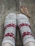 在被编织的羊毛袜子和橡木叶子的脚 免版税库存图片