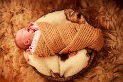 在被编织的围巾啼声盖的新出生的婴孩 库存照片