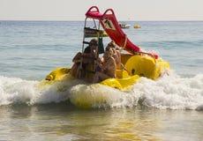 在被聘用的Pedalos战斗的假日制造商与出去的接踵而来的海浪入更加镇静的水在海滩在Albuferia葡萄牙 免版税库存图片