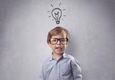 在被草拟的灰色墙壁前面的聪明的孩子 免版税库存照片