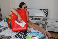 在被过度充填的手提箱旁边的女孩 准备好旅行 旅途的早晨好 库存图片