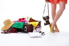 在被过度充填的手提箱旁边的妇女的腿 免版税库存照片