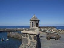 在被铺的海滨人行道的老铜大炮与发射孔塔,石头 库存照片