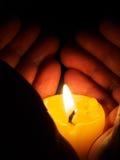 在被阐明的蜡烛附近的手 图库摄影