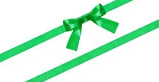 在被隔绝的两条对角丝绸带的绿色弓结 免版税图库摄影