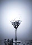从在被隔绝的马蒂尼鸡尾酒玻璃的冰块飞溅 免版税库存图片