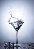 从在被隔绝的马蒂尼鸡尾酒玻璃的冰块飞溅 图库摄影