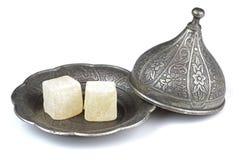在被雕刻的传统无背长椅样式的土耳其快乐糖仿造了在白色背景隔绝的金属片 免版税图库摄影