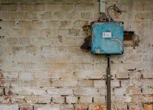 在被风化的墙壁上的老坏生锈的开关盒 免版税库存照片