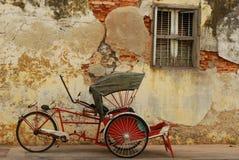 在被风化的墙壁前面的红色trishaw 库存照片