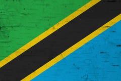 在被风化的木头的一面土气老坦桑尼亚旗子 免版税库存图片