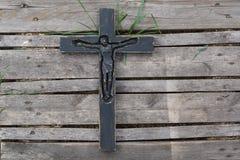 在被风化的木板条背景的黑木耶稣受难象 库存照片