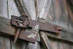 在被风化的木毂仓大门的老生锈的锁 库存照片