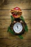 在被风化的木背景的圣诞节花圈杉树分支葡萄酒闹钟红色光滑的苹果计算机肉桂条茴香星 免版税库存图片