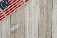 在被风化的木背景的美国爱国老旗子 库存照片
