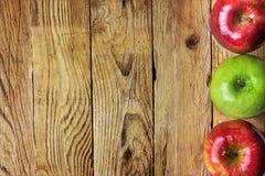 在被风化的木背景的边界框架安排的成熟五颜六色的红色绿色苹果 感恩收获秋天秋天 库存图片