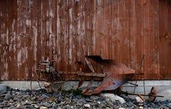 在被风化的木谷仓墙壁前面的一个老和生锈的马犁 图库摄影