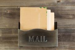 在被风化的木头的老金属邮箱 免版税库存照片