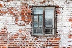 在被风化的红砖墙壁上的木窗口绘了白色 免版税库存照片
