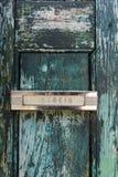 在被风化的老木门的邮件交付槽在大厦在里斯本,葡萄牙 免版税图库摄影