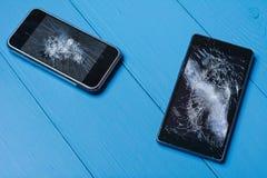 在被绘的木桌上的两个残破的手机 免版税库存图片