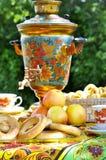 在被仿造的桌布的花梢俄国式茶炊用茶和百吉卷 免版税库存图片