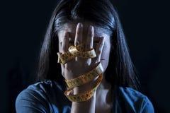 在裁缝措施磁带年轻人沮丧的和担心的女孩遭受的厌食或善饥癖营养dis的覆盖物面孔包裹的手 免版税库存照片