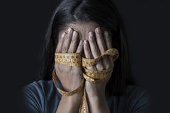 在裁缝措施磁带年轻人沮丧的和担心的女孩遭受的厌食或善饥癖营养dis的覆盖物面孔包裹的手 免版税图库摄影