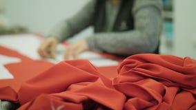 在裁缝的背景的珊瑚布料在焦点外面的在工作 股票视频