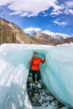在裂缝里面的女性在冰冰川冰岛 库存图片