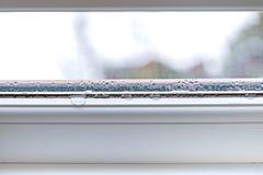 在装双面玻璃玻璃特写镜头pvc的窗口的结露 库存图片