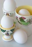 在装煮好带壳蛋之小杯的煮沸的白鸡蛋有雄鸡的 图库摄影