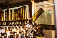 在装瓶机的未贴标签的玻璃瓶在现代酿酒厂 库存照片