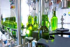 在装瓶机的白葡萄酒在酿酒厂 免版税库存照片
