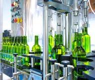 在装瓶机的白葡萄酒在酿酒厂 免版税库存图片