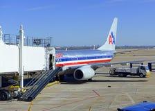 在装载它的货物的柏油碎石地面的商业喷气机在机场在飞行前 库存图片