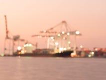 在装载由起重机的焦点容器外面在晚上,贸易 免版税库存照片