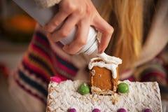 在装饰圣诞节曲奇饼房子的女孩的特写镜头 免版税库存图片