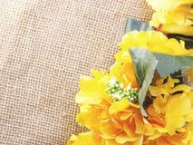 在装饰桌布的Yelow玫瑰色花在袋装的背景空间和构成 免版税库存图片