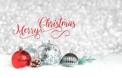 在装饰球的红色圣诞快乐在银的白色毛皮 免版税图库摄影