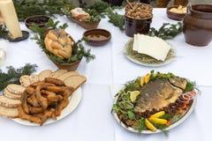 在装饰用圣诞树的桌上的圣诞节食物 图库摄影